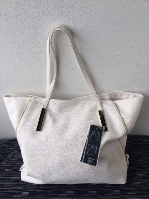 Bílá trendy kabelka se zlatou kombinací.